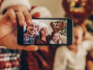 Vater macht Handy-Foto von der Familie zu Weihnachten