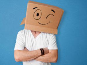 Mann mit Pappkarton über dem Kopf, auf den ein freundlich zwinkerndes Gesicht gemalt ist