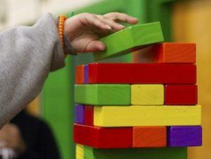 Kinderhand legt weiteren Stein auf Bauklotzturm