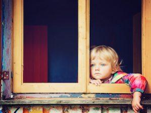 Kleines Kind mit ernstem Gesichtsausdruck schaut aus offenem Fenster