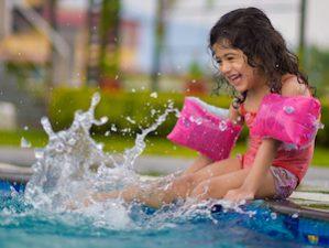 Mädchen mit Schwimmflügeln sitzt am Poolrand